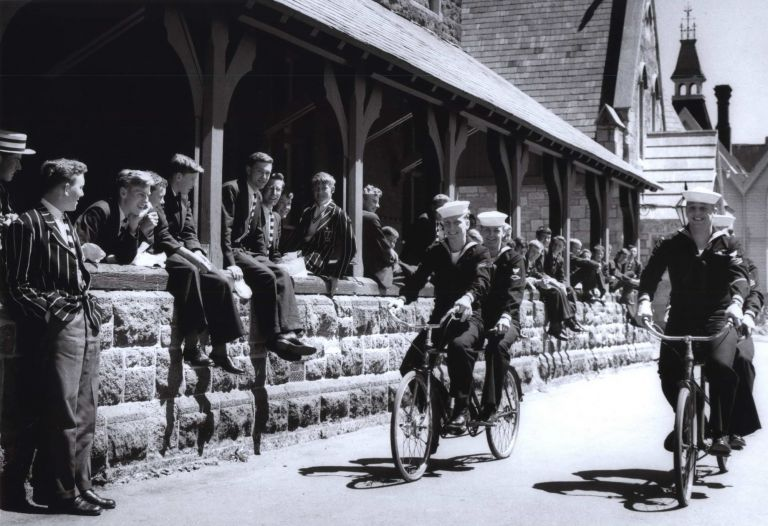 "US Navy Sailors Of ""Operation Deep Freeze"" Riding Their Tandems Through The Private Grounds Of Christ's College, Christchurch [NZ]. Robin Smith, b.1927 NZ/Aust."