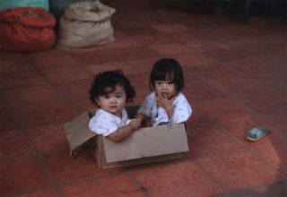 Two Little Girls In Their Cardboard Box Crèche, Roluos Market, Near Siem Reap, Cambodia. Robin...